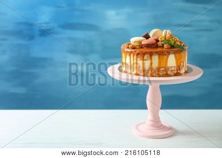 Stand with delicious caramel cake on table against color wall