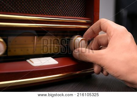 Person tuning retro radio, closeup