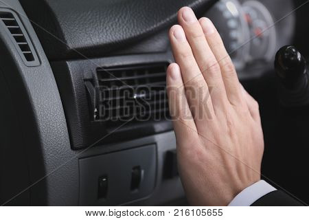 Man turning on air conditioner in car, closeup