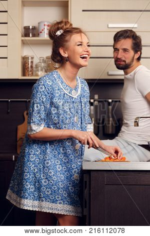 Photo of happy loving couple cutting vegetables in kitchen