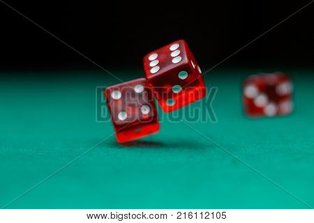 Photo of dice falling on green table