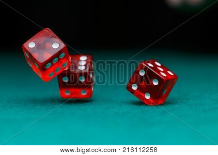 Image of several red dice falling on green table on black background