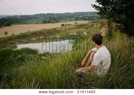 Young man sitting in the grass on the edge of the hill. overlook.