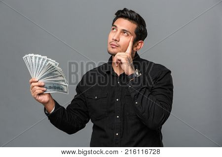 Image of handsome young thinking concentrated man standing isolated over grey wall. Looking aside holding money.