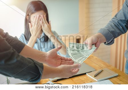 Business partners meeting and passing money for new startup project with one businesswoman hands closing the eyes in office room.Bribery and corruption concepts estate concept financial concept.