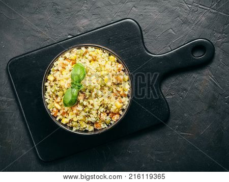 Top view of cauliflower rice with vegetables. Organic paleo Cauliflower Rice with corn, green peas and carrots on black cutting board over black concrete background. Copy space.