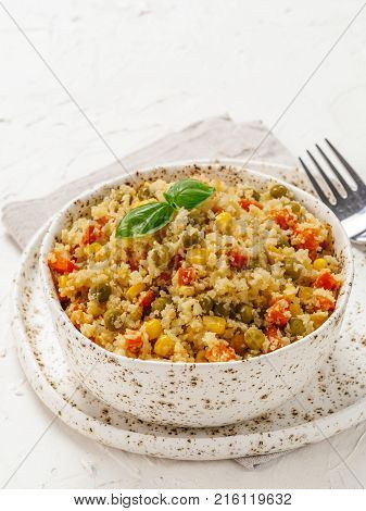 Close up view of cauliflower rice with vegetables. Organic paleo Cauliflower Rice with corn, green peas and carrots on white concrete background. Copy space.
