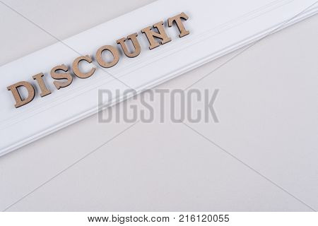Word DISCOUNT abstract wooden letters, white background copy space