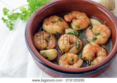 prawns or shrimps with garlic and parsley in sherry sauce in a tapas bowl spanish appetizer gambas al ajillo white tablecloth selected focus narrow depth of field