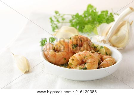 shrimps with garlic olive oil and parsley in sherry sauce in a white bowl spanish tapas appetizer gambas al ajillo white napkin and herb garnish in the background copy space selected focus narrow depth of field