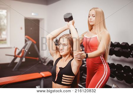 Dumbbells. A trainer girl helps to do exercises with dumbbells. Concept team of athletes engaged in body fitness