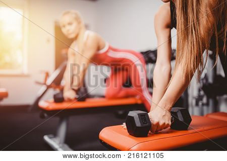 Dumbbells. Girls are engaged in a group, a body of bodybuilding with dumbbells. Elbow bending at the elbow body fitness