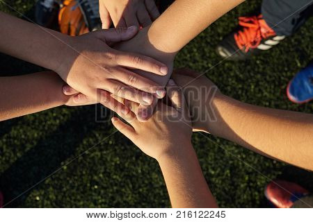 Close-up of many children's hands holding together as a football team on court.
