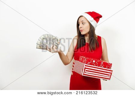 Young Disconfused Frustrated Woman In Red Dress And Christmas Hat Holding Gift Boxes And Money Bankn