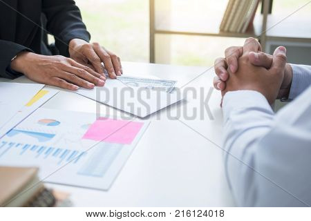 Bribery and corruption concept bribe in the form of dollar bills Businessman giving money in the envelope while making deal to agreement a real estate contract and financial corporate.