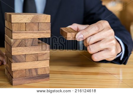 Alternative risk concept plan and strategy in business Risk To Make Buiness Growth Concept With Wooden Blocks Images of hand of businesspeople placing and pulling wood block on the tower.