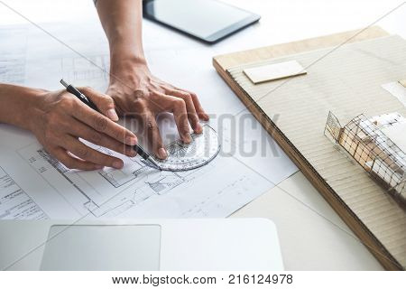 Architect working on blueprint Engineer working with engineering tools for architectural project on workplace Construction concept - building project blueprints ruler and dividers.