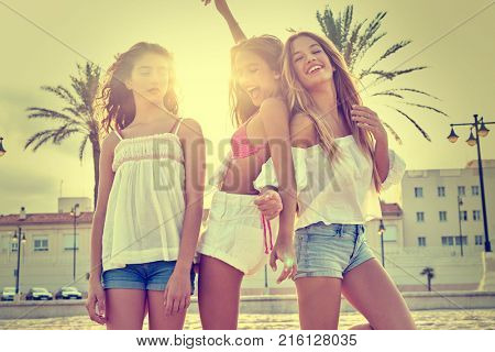 Best friends teen girls having fun on a beach sand at sunset filtered image