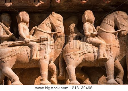 Famous military art bas relieves, Lakshmana Temple, Khajuraho, India. Battle scene with warriors, horsemen and elephat riders. Unesco World Heritage. Famous landmark in India. Temple of love.