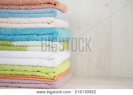 Wash fresh towels in a pile with copy space. Gently folded clean towels on a light wooden surface. Terry towels in the bathroom. Accessories for wiping after taking a shower.