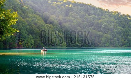 Plitvice Lakes National Park, Croatia - August 30, 2017: A couple is enjoying evening row boat ride on a lake in Plitvice Lakes National Park, Croatia