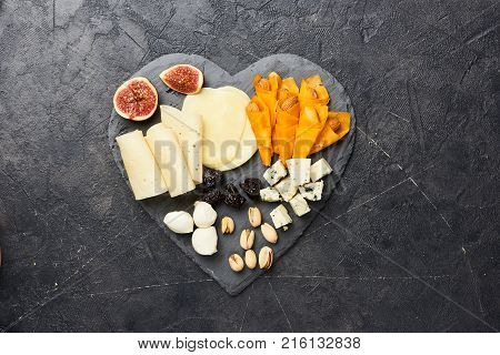 Cheese plate antipasti snack with Blue cheese, olives, figs on black board. Party. Top view.