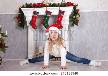 Gymnastic pose stretch. Little blonde girl in the Santa hat doing cross-twine exercising. Doing a full split in Christmas interior