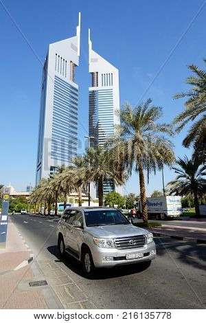 DUBAI UAE - NOVEMBER 19: The Emirates Towers and Land Cruiser car on November 19 2017. The Emirates Towers complex is set in over 570000 m2