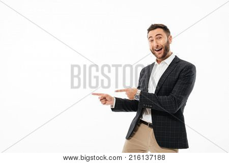 Portrait of a cheerful happy man standing and pointing finger away isolated over white background