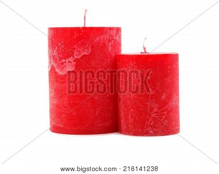 Two different in size, red wax candles with a wick on an isolated white background, candles stand next to each other, one can see their difference in size, concept of holidays, new year