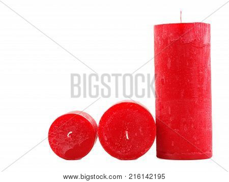 Three different in size red wax candles with a wick, lie on isolated white background, one stands, two candles lie a fitter to the camera, different in diameter, concept of holidays, new year poster