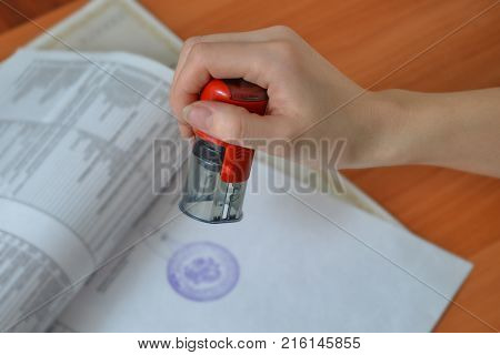 Female hand hold rubber stamps over documents and papers at office table, closeup detail shoot