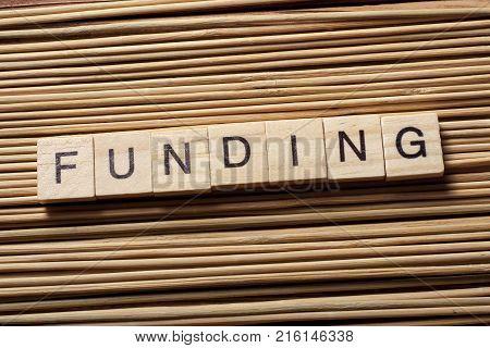 Word FUNDING written on wooden cubes. Finance concept