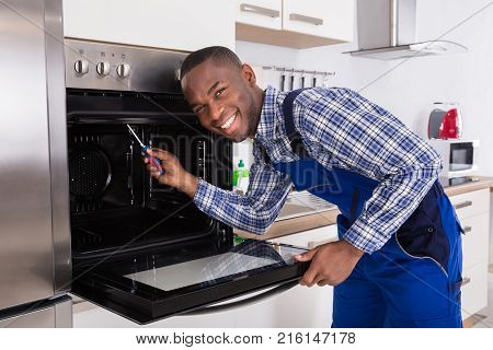 Young Repairman With Screwdriver Fixing Kitchen Oven