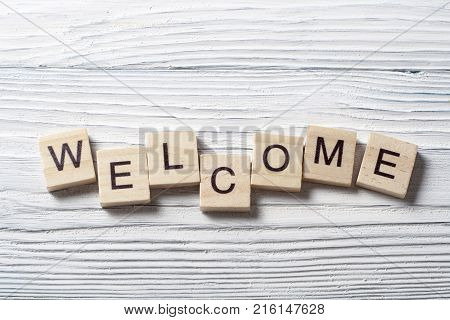 Word WELCOME written on wooden cubes.Wood abc. Holidays and education concept.