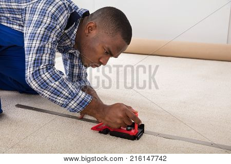 Young Craftsman Installing Carpet On Floor Using Fitter poster