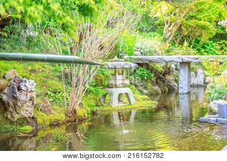Japanese culture concept. Close up of traditional japanese bamboo fountain in Take-dera or hokoku-ji temple garden. Kamakura, Japan. Japanese temple and buddhism concept.