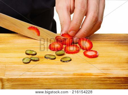 Close-up of the chef's chef's hands cut into a wooden board, where already there is grapes, a ripe strawberry