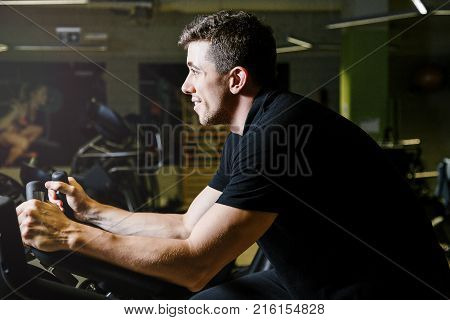 Boy on a stationary bike. A man is engaged in sports in the gym. Work of personal trainer. Portrait Of Personal Trainer In Sports Outfit In Fitness Center Gym Standing Strong.