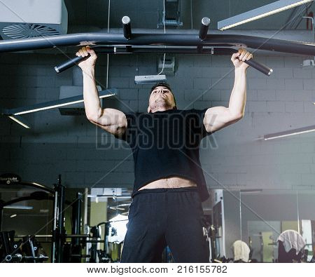 Tightening on the crossbar. Sports exercises with a crossbar.   Work of personal trainer. Portrait Of Personal Trainer In Sports Outfit In Fitness Center Gym Standing Strong.