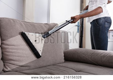 Housewife's Hand Cleaning Sofa With Vacuum Cleaner At Home