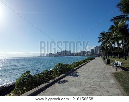 Path along the water at Sans Souci State Recreational Park with Waikiki in the distance on Oahu Hawaii. poster