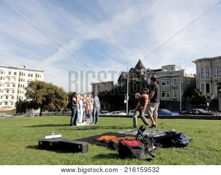 San Francisco - November 9 2011: People pose for photo with cast of Full House in Alamo Square where the opening scene of the popular show shows their families house to be.