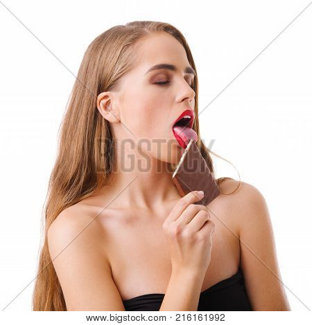 Close-up of a young girl, blonde, with closed eyes, with a nurse, tongue, licks a piece of chocolate, isolated on a white background.