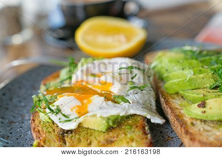 Breakfast served and started poached egg with yoke running onto sliced avocado and toast in selective focus.