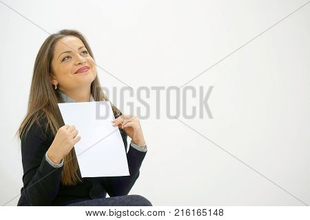 Smiling woman reading letter while sitting on sofa in front of laptop. Happy lady enjoying good news in written notice. Euphoric girl happy after reading good news in written letter loan approvale