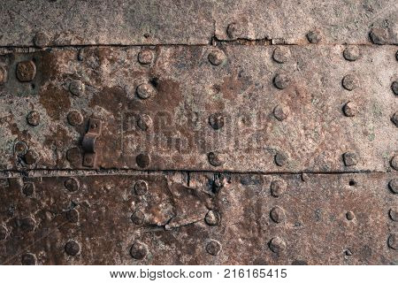 Rusty metal texture. Studded iron plate. Rivets on old rusty metal door. Weathered aged grunge texture