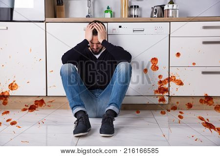 Disappointed Young Man Sitting On Kitchen Floor With Spilled Food In Kitchen