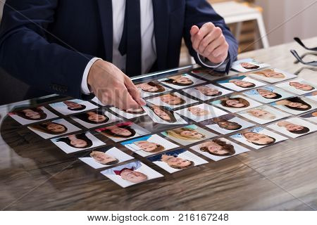 Close-up Of Businessperson Choosing Photograph Of Candidate On Desk In Office