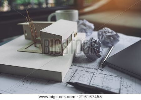 An architecture model with shop drawing paper and laptop on table in office